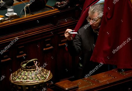 Northern League party lawmaker Umberto Bossi, holds his ballot as he leaves the electoral booth during a voting session electing the new Italian President in Rome, . Lawmakers cast ballots Thursday for a new Italian president in a vote testing Premier Matteo Renzi's ability to rally his divided party behind his reform agenda and a single candidate who is also agreeable to ex-Premier Silvio Berlusconi. Polling was expected to last at least until Friday or Saturday since the threshold slips from a two-thirds majority to a simple majority after three rounds of voting