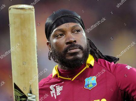 """Stock Photo of West Indies Chris Gayle waves his bat to the crowd as he leaves the field after he was dismissed for 61 runs while batting against New Zealand during their Cricket World Cup quarterfinal match in Wellington, New Zealand. The head of Cricket Australia has joined the criticism of Gayle's suggestive comments to a female reporter during an interview broadcast live on Australian television, saying the former West Indies captain's behavior bordered on harassment and were inappropriate in the workplace. After scoring 41 from 15 deliveries in the Melbourne Renegades win over the Hobart Hurricanes in Australia's domestic Twenty20 Big Bash League, the former West Indies captain suggested to television reporter Mel McLaughlin that the pair go out for a drink and made remarks about her appearance during a post-innings interview. He added, """"Don't blush, baby"""" during an awkward pause in the interview"""