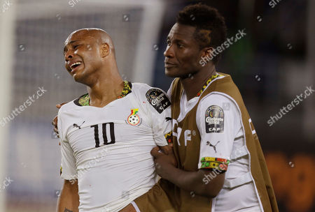 Ghana's Andre Ayew, left, is consoled by team mate Asamoah Gyan, right, after they lost their African Cup of Nations final soccer match to Ivory Coast in Bata, Equatorial Guinea