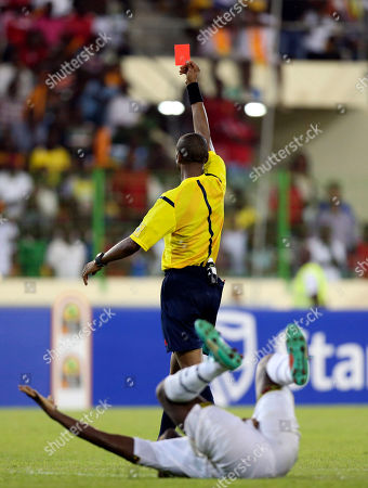 Referee Janny Braimah issues a red card to Guinea's goalkeeper Naby Yattara, not pictured, after a tackled on Ghana's Asamoah Gyan, below, during their African Cup of Nations quarter final soccer match at the Estadio De Malabo, Equatorial Guinea