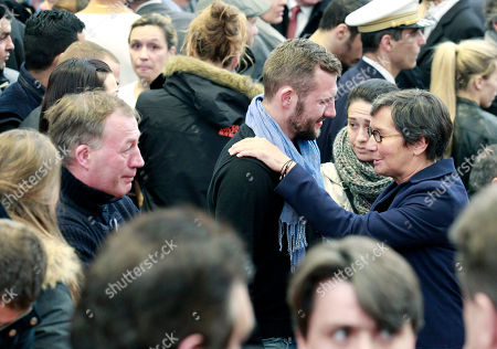 Stock Photo of Former French sports minister Valerie Fourneyron, right, comforts Adriani Vastine, the brother of Alexis Vastine during a remembrance ceremony at the French National Institute For Sports, in Paris, . Olympic champion swimmer Camille Muffat, Olympic bronze-medalist boxer Alexis Vastine and pioneering sailor Florence Arthaud were among 10 people who died as two helicopters filming a reality show crashed in a remote part of Argentina on Monday. Watching at left is Alexis Vastine's father Alain