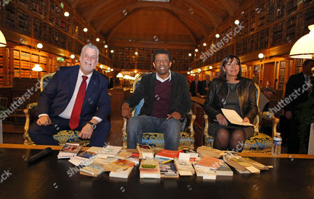 Quebec Premier, Philippe Couillard, left, Haitian-born writer Dany Laferriere, center, and Paris Mayor, Anne Hidalgo, pose for photographers prior to a literary meeting in the library of Paris City Hall, . Philippe Couliard is on a five-day official visit to France
