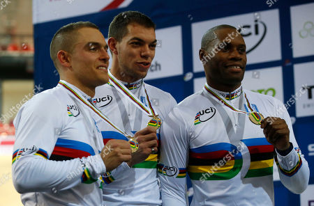 French team Michael D'Almeida, left, Kevin Sireau, center, and Gregory Bauge, right, pose with their medals on the podium during the Men's Team Sprint race medal ceremony at the Track Cycling World Championships in Saint-Quentin-en-Yvelines, outside Paris, France, . France won gold, New Zealand won silver and Germany won bronze