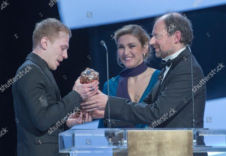 "French actor Kevin Azais reacts after winning the Best Male Newcomer award for ""Les Combattants"" (Love at First Fight) next to French actress Julie Gayet, center, and French actor Denis Podalydes during the 40th Cesar Film Awards at Theatre du Chatelet in Paris, France,. This annual ceremony is presented by the French Academy of Cinema Arts and Techniques"