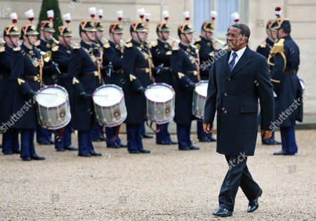 Tanzanian President Jakaya Mrisho Kikwete reviews an honor guard as he arrives at the Elysee Palace for a meeting with French President Francois Hollande in Paris