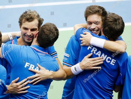 Julien Benneteau, left, and Nicolas Mahut hug their team mates after beating Germany's Benjamin Becker and Andre Begemann in the doubles during a first round tennis Davis Cup match between Germany and France in Frankfurt, Germany, . France has now an unassailable 3-0 lead and advances to the next round