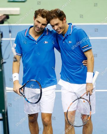 Julien Benneteau, left, and Nicolas Mahut hug each other after beating Germany's Benjamin Becker and Andre Begemann in the doubles during a first round tennis Davis Cup match between Germany and France in Frankfurt, Germany, . France has now an unassailable 3-0 lead and advances to the next round