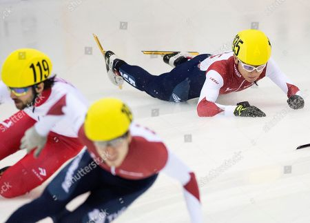 Olympic champion Victor An of Russia, right, crashes besides Olympic champion Charles Hamelin of Canada, (119), during the men's 1,000 meters semi final race at the World Cup short track speed skating championship in Dresden, Germany