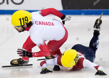 Olympic champion Victor An of Russia, right, crashes beside Olympic champion Charles Hamelin of Canada, left, during the men's 1,000 meters semi final race at the World Cup short track speed skating championship in Dresden, Germany