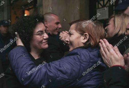 On cleaning workers, laid off by the Finance Ministry, hug new Deputy Finance Minister Nadia Valavani, left, and the new Greek Finance Minister Yanis Varoufakis, background, outside the National Economy Ministry in Athens. Greece's Alternate Finance Minister Nadia Valavani has resigned on Wednesday, July 15, 2015 from government in protest over the austerity measures the country is asked to implement in exchange for a bailout