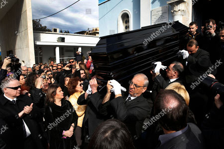 Mourners applaud as pallbearers carry the coffin of singer Demis Roussos during his funeral procession in Athens, . Several hundred mourners gathered to bid a final farewell to the renowned singer. Roussos, whose often high-pitched pop serenades won him household recognition in the 1970s and 1980s across Europe and beyond and who sold more than 60 million records, died earlier this week at the age of 68