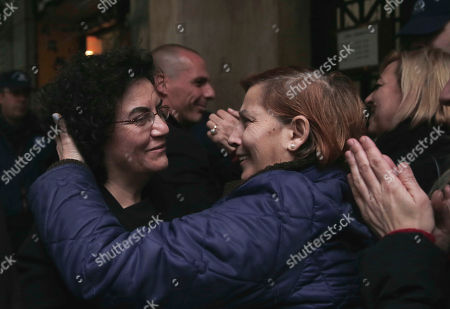 Cleaning workers, laid off by the Finance Ministry, hug new Deputy Finance Minister Nadia Valavani, left, and the new Greek Finance Minister Yanis Varoufakis, background, outside the National Economy Ministry in Athens, on . Varoufakis announced that the government will re-hire them to the public sector. Dozens of the nearly 600 formerly state-employed cleaning ladies, who were sacked 18 months ago amid austerity cuts, have kept up the protest against their dismissals for more than eight months. Their court battle became a symbol of anti-austerity protests in Greece