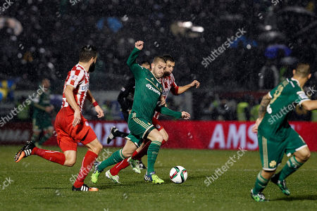Stock Picture of Panathinaiko's Mladen Petric from Croatia, center, tries to control the ball against Olympiakos' Luka Milivojevic from Serbia, rear, during their Greek Super League soccer match at the Apostolos Nikolaides stadium in Athens, Sunday, Feb.22, 2015