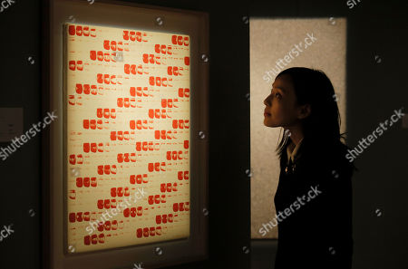 """A woman looks at a painting entitled """" From Point """" by the South Korean artist Lee Ufan during the Sotheby's """" Gutai and Its Legacy and Avant Garde Asia: Lines of Korean Masters """" exhibition in Hong Kong, . The exhibitions present post-war Japanese and Korean abstract arts"""
