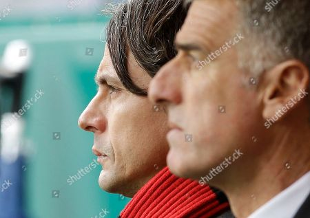 AC Milan coach Filippo Inzaghi, left, and his assistant Mauro Tassotti wait the start of the Serie A soccer match between AC Milan and Cesena at the San Siro stadium in Milan, Italy