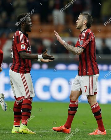 AC Milan's Jeremy Menez, right, celebrates with his teammate Sulley Muntari after scoring on a penalty during a Serie A soccer match between AC Milan and Hellas Verona, at the San Siro stadium in Milan, Italy