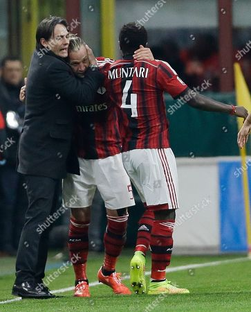 AC Milan's Philippe Mexes, center, celebrates with AC Milan coach Filippo Inzaghi, left, and his teammate Sulley Muntari after scoring during a Serie A soccer match between AC Milan and Hellas Verona, at the San Siro stadium in Milan, Italy