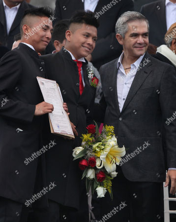 Stock Photo of Mexico City's Mayor Miguel Angel Mancera, right, accompanies Luis Enrique, center, and Yonathan Olvera, left, as they hold their marriage certificate after getting married along with other 1,690 couples on Valentine's day in Mexico City's main square, the Zocalo, . The Mexico City government organized the massive collective wedding as part of the Valentine's day celebrations