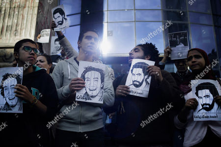 "Journalists hold placards of photojournalists Mahmoud Abu Zied, known as ""Shawkan,"" left, and Ahmad Jamal Ziyadah to protest against their detention during a rally in front of the Syndicate of Journalists building in Cairo, Egypt, . Shawkan, an Egyptian freelance photographer, was arrested on Aug. 14, 2013, while covering the government forces' deadly dispersal of sit-in supporters of the ousted President Mohammed Morsi at the Rabaah al-Adawiya mosque"