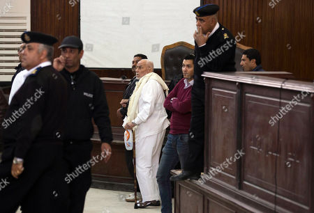 Stock Image of Mohammed Mahdi Akef Former Muslim Brotherhood Supreme Guide Mohammed Mahdi Akef, center, appears in a courtroom accompanied by policemen in Cairo, Egypt, . An Egyptian court has sentenced four members of the banned Muslim Brotherhood organization to death and 14 to life in prison. Brotherhood Supreme Guide Mohammed Badie and his deputy Khairat al-Shater were among those sentenced to life, along with former lawmaker Mohammed el-Beltagy and party head Saad el-Katatni and his deputy, Essam el-Erian