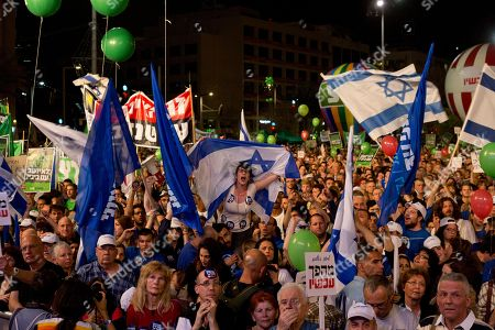 """People shout slogans during a rally in Rabin's square in Tel Aviv, Israel, . Tens of thousands of Israelis are gathering at a Tel Aviv square under the banner """"Israel wants change"""" and calling for Prime Minister Benjamin Netanyahu to be replaced in March 17 national elections. Saturday night's rally at Rabin Square is the highest profile demonstration yet in the run-up to the election. It is organized by a non-profit organization seeking to change Israel's priorities and refocus on health, education, housing and the country's cost of living. Though not officially endorsed by any political party, it drew mostly supporters of leftist and centrist parties. The rally's keynote speaker is former Mossad chief Meir Dagan who recently slammed Netanyahu's conduct and called him """"the person who has caused the greatest strategic damage to Israel"""