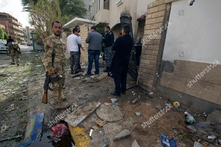 """Security Personnel inspect the Iranian ambassador's house after it received minor damage from an improvised explosive device placed among garbage bags, in Tripoli, Libya, . Iran's Foreign Ministry spokeswoman Marzieh Afkham condemned the """"terrorist"""" attack, which she said claimed no lives. She called on political rivals in Libya to form a national unity government to end the country's escalating chaos"""