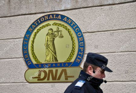 On, a policeman walks by the logo of the anti-corruption prosecutors office before the arrival of Elena Udrea a 41-year-old Romanian politician who gained notoriety due to her close relationship with Traian Basescu, Romania's president from 2004 to 2014 in Bucharest, Romania. Udrea, a former Romanian tourism minister and presidential candidate was detained for 24 hours late Tuesday after she entered the anti-corruption prosecutor's office to answer charges of money laundering and influence peddling