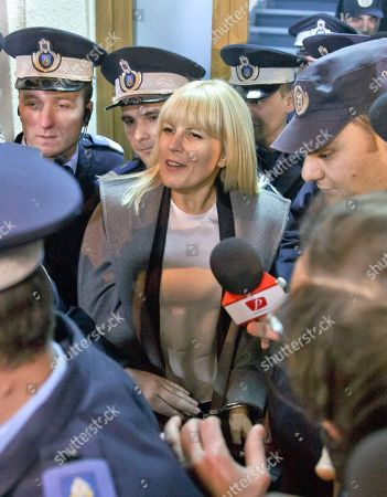 On, Elena Udrea a 41-year-old Romanian politician who gained notoriety due to her close relationship with Traian Basescu, Romania's president from 2004 to 2014 is escorted by policemen as she exits, handcuffed, the anti-corruption prosecutor's office in Bucharest, Romania. Udrea, a former Romanian tourism minister and presidential candidate was detained for 24 hours late Tuesday after she entered the anti-corruption prosecutor's office to answer charges of money laundering and influence peddling