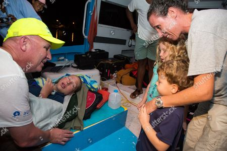 Stock Photo of Athlete tries for record breaking swim in the Bahamas Australian ultra-marathon swimmer Chloe McCardel is comforted by her husband Paul McQueeney, left while Lily Hope, 6, and Luke Hope, 4, along with their Mother Michelle Lakin Hope, get the chance to meet McCardel as she rests on a boat off the Nassau coastline early after completing her world record marathon swim attempt. McCardel was severely dehydrated and fatigued, in addition to having suffered multiple jellyfish bites and the affects of sunstroke during the 128 kilometer (80 mile) swim from the island of Eleuthera to New Providence