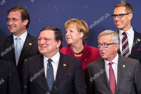 From left, Portuguese Prime Minister Pedro Passos Coelho, European Commission President Jose Manuel Barroso, German Chancellor Angela Merkel, European Commission President elect Jean-Claude Juncker and Finnish Prime Minister Alexander Stubb pose during a group photo at an EU summit in Brussels, on . EU leaders will gather Thursday for a two-day summit in which they will discuss Ebola, climate change and the economy