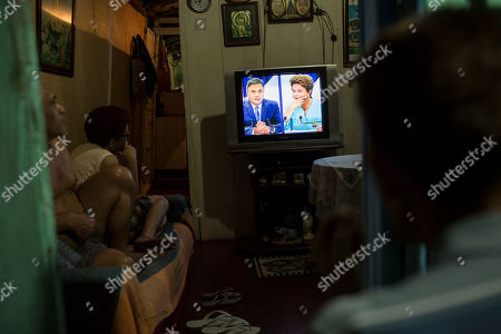Stock Picture of Residents in their home watch a live presidential debate on TV between candidates Aecio Neves, left, and Brazil's current President Dilma Rousseff in the Dona Marta slum of Rio de Janeiro, Brazil, ahead of a presidential election run-off on Sunday, Oct. 26. The tightest and most unpredictable presidential election since Brazil's return to democracy three decades ago is now in the hands of lower middle class voters who remain torn about which candidate they'll back just days before the ballot