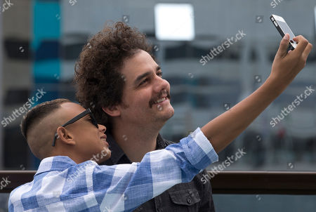"""Wagner Moura, Gabriel Weinstein Gabriel Weinstein, front left, who stars in the film """"Trash,"""" takes a selfie with Brazilian actor Wagner Moura during a photo call to promote their new film in Rio de Janeiro, Brazil, . The latest film by Stephen Daldry may be the anti-picture postcard vision of Rio de Janeiro, exposing the dark underbelly of police violence and crushing poverty, but the Oscar-nominated British director managed to hold onto his rosy vision of the city"""