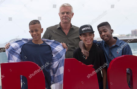 """Stephen Daldry Film director Stephen Daldry poses for photos with the children featured in his film """"Trash,"""" Rickson Tevez, front center, Gabriel Weinstein, left, and Eduardo Luis as they gather for a photo call promoting the new film in Rio de Janeiro, Brazil, . Daldry's latest film may be the anti-picture postcard vision of Rio de Janeiro, exposing the dark underbelly of police violence and crushing poverty, but the Oscar-nominated British director managed to hold onto his rosy vision of the city"""