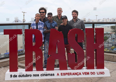 """Stephen Daldry, Wagner Moura, Selton Mello The crew from the new film """"Trash"""" pose during a photo call to promote their new film in Rio de Janeiro, Brazil, . In the back row from left are actor Wagner Moura, Director Stephen Daldry, and actor Selton Mello. In the front row from left are children featured in the film, Gabriel Weinstein, Eduardo Luis and Rickson Tevez. Daldry's latest film may be the anti-picture postcard vision of Rio de Janeiro, exposing the dark underbelly of police violence and crushing poverty, but the Oscar-nominated British director managed to hold onto his rosy vision of the city"""
