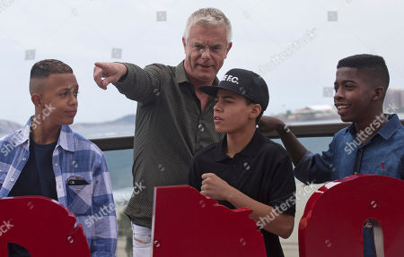 """Stephen Daldry Film director Stephen Daldry points as he speaks with the children featured in his film """"Trash,"""" Rickson Tevez, front center, Gabriel Weinstein, left, and Eduardo Luis as they gather for a photo call promoting the new film in Rio de Janeiro, Brazil, . Daldry's latest film may be the anti-picture postcard vision of Rio de Janeiro, exposing the dark underbelly of police violence and crushing poverty, but the Oscar-nominated British director managed to hold onto his rosy vision of the city"""