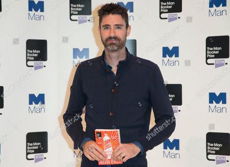Man Booker prize 2014 nominee US author Joshua Ferris holds his book 'To Rise Again at a Decent Hour' during a photocall for the Man Booker Prize for fiction 2014 at the Royal Festival Hall in London, . The winner will be announced in London on Tuesday