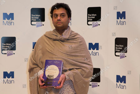 Stock Image of Man Booker prize 2014 nominee British author Neel Mukherjee holds his book 'The Lives of Others', during a photocall for the Man Booker Prize for fiction 2014 at the Royal Festival Hall in London, . The winner will be announced in London on Tuesday