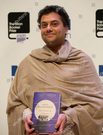 Man Booker prize 2014 nominee British author Neel Mukherjee holds his book 'The Lives of Others' during a photocall for the Man Booker Prize for fiction 2014 at the Royal Festival Hall in London, . The winner will be announced in London on Tuesday
