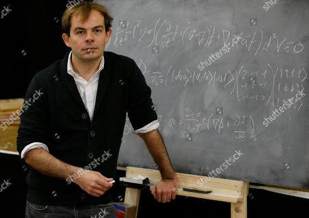 Angus Jackson, Director of new play 'Oppenheimer' poses with a board of equations, at a rehearsal studio in London, . Jackson is directing a new play the Royal Shakespeare Company is doing about the physicist Robert Oppenheimer, who led the team that developed the first nuclear weapon