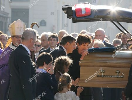 Bernadette de Margerie, widow of former Total SA Chief Executive Christophe de Margerie, gestures at her husband's coffin, comforted by Elysee Palace secretary general Jean-Pierre Jouyet, after the funeral service at Saint Sulpice church in Paris, France. De Margerie was killed in a plane crash at a Moscow airport. The private jet he was travelling on hit a snowplow on take-off