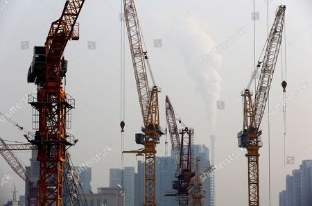 Cranes stand on a construction site as smoke belches from a coal-fired power station on a hazy day in Beijing, China . China National Development and Reform Commission Vice Chairman Xie Zhenhua told reporters Tuesday that China will increase use of renewable energy and rely less on coal to ensure it meets its carbon emissions peak in 2030, as a new United Nations report warned the world is failing to prevent dangerous levels of global warming