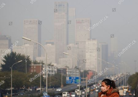 A woman wearing a mask to protect herself from pollutants walks on a pedestrian bridge as buildings at Beijing's Central Business District are shrouded in haze . China National Development and Reform Commission Vice Chairman Xie Zhenhua told reporters Tuesday that China will increase use of renewable energy and rely less on coal to ensure it meets its carbon emissions peak in 2030, as a new United Nations report warned the world is failing to prevent dangerous levels of global warming