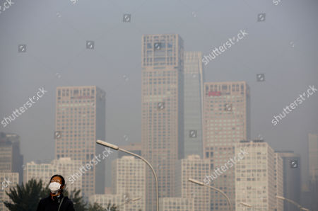 A woman wearing a mask to protect herself from pollutants stands on a pedestrian bridge as buildings at Beijing's Central Business District are shrouded in haze . China National Development and Reform Commission Vice Chairman Xie Zhenhua told reporters Tuesday that China will increase use of renewable energy and rely less on coal to ensure it meets its carbon emissions peak in 2030, as a new United Nations report warned the world is failing to prevent dangerous levels of global warming