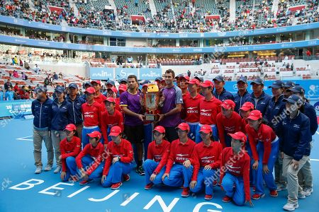 Horia Tecau, Jean-Julien Rojer Horia Tecau, center right, of Romania and Jean-Julien Rojer, center left, of the Netherlands holding their trophy pose with ball boys and girls and others after winning over the French pair of Michael Llodra and Nicolas Mahut in the men's doubles final at China Open tennis tournament at the National Tennis Stadium in Beijing, China