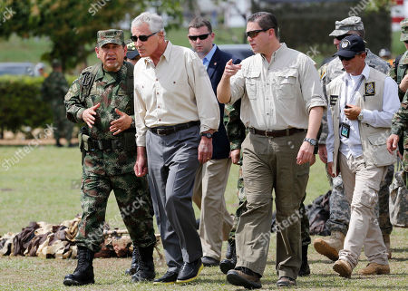 Chuck Hagel, Juan Pablo Rodriguez, Juan Carlos Pinzon Colombian Armed Forces Commander, Gen. Juan Pablo Rodriguez, left, and Defense Minister Juan Carlos Pinzon, right, lead a tour for U.S. Defense Secretary Chuck Hagel, center, at the Tolemaida military base, in Melgar, Colombia, . Hagel is on a six-day, three-country trip to South America. Hagel will also travel to Chile and Peru, where he will attend a conference of defense ministers from the Americas