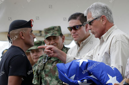 Chuck Hagel, Juan Carlos Pinzon U.S. Defense Secretary Chuck Hagel, right, talks to an army soldier as Colombia's Defense Minister Juan Carlos Pinzon, second right, watches, at the Tolemaida military base, in Melgar, Colombia, . Hagel is on a six-day, three-country trip to South America. Hagel will also travel to Chile and Peru, where he will attend a conference of defense ministers from the Americas