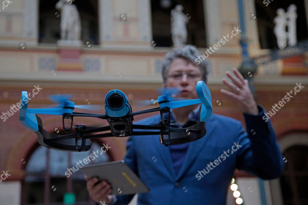 Parrot CEO Henri Seydoux guides his Bebop Parrot drone with an IOS tablet during a presentation to the press in Paris, France, . The new Parrot Bebop drone, quadcopter type drone with a fish eye camera benefits from an exclusive 3-axes image stabilization system that maintains a fixed angle of the view, regardless of the inclination of the drone and its movements caused by wind turbulence