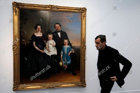 """A visitor walks by """"Family portrait with Red Noses"""" by artist Hans-Peter Feldmann as part of the FIAC, the International Fair of Contemporary Art, during the presentation to the press, in Paris, . The fair opens Oct. 23 and ends on Oct. 26"""
