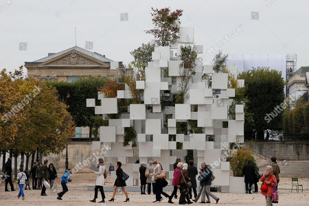People walk past Many Small Cubes by Japanese architect Sou Fujimoto as it is displayed in the Tuileries Garden of the Louvre Museum as part of the FIAC, the International Fair of Contemporary Art, in Paris, . The fair opens Oct. 23 and ends on Oct. 26