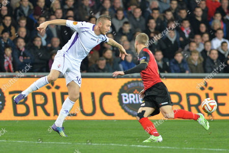 Fiorentina's midfielder Jasmin Kurtic, left, controls the ball past Guingamp's Lars Jacobsen during their Europa League Group K soccer match in Guingamp, western France